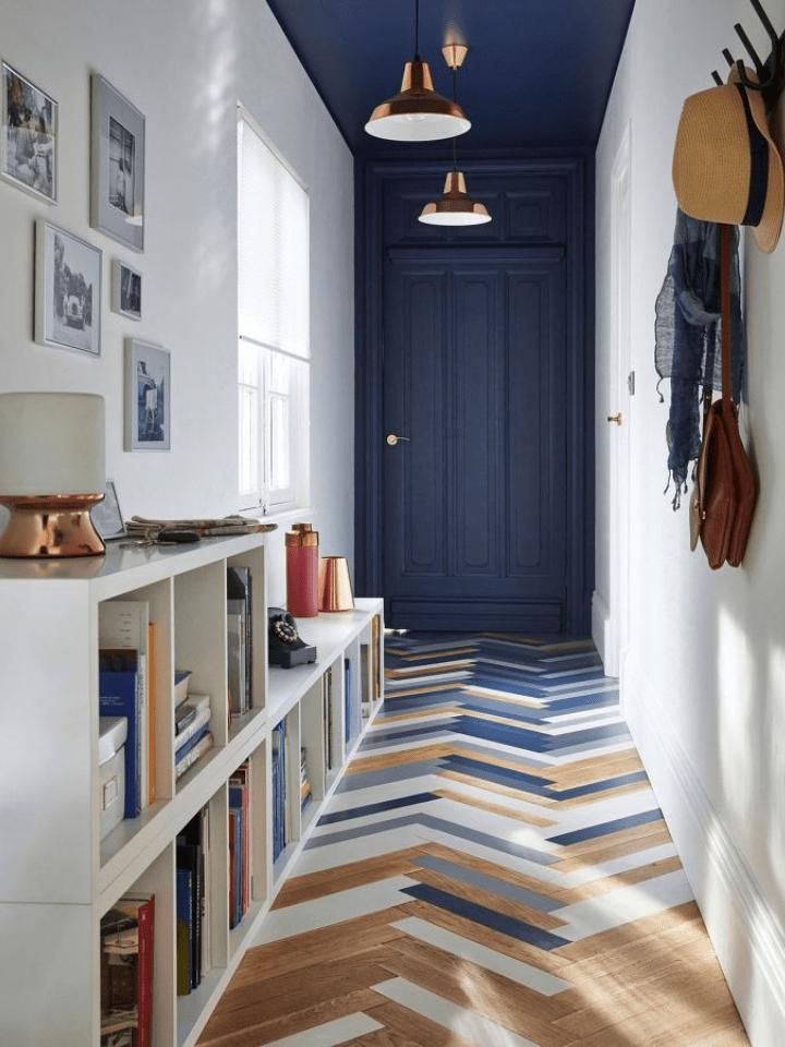 recibidor pequeño y funcional con suelo en espiga y puerta azul