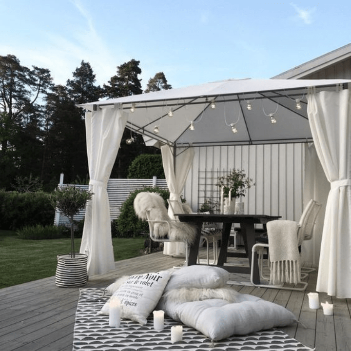 terraza acogedora con cenador de forja y cortinas y techo blancos